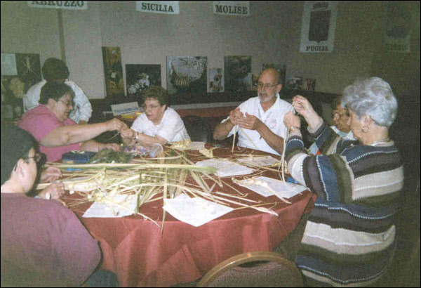 Anna Marie Fiori (second from left) and Gene Fedeli (third from right) teach participants to weave p